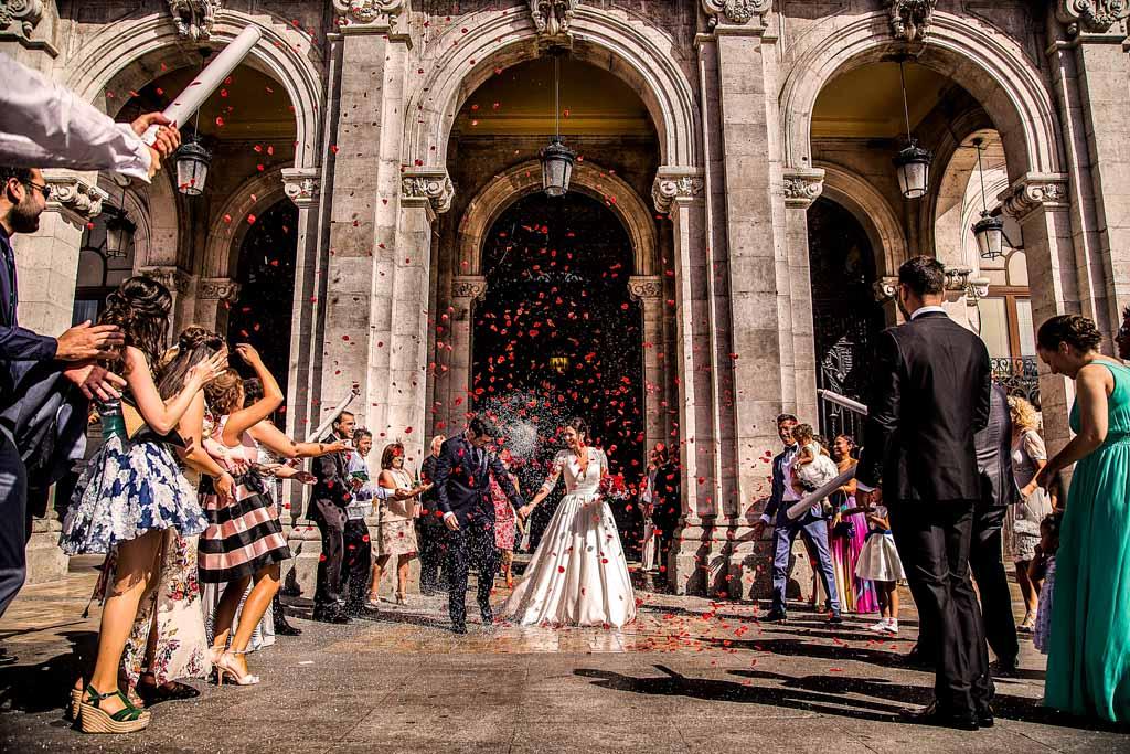 Fotografia de boda a la puerta del ayuntamiento de Valladolid, los invitados tirando arroz a los novios